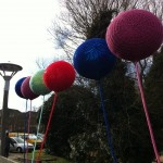 Knitted balloons swaying in the wind along the bridge